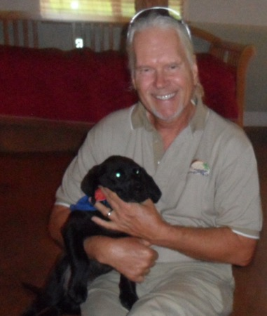 Makana Aloha founder, Gunars Valkirs with a puppy in training at Assistance Dogs of Hawaii