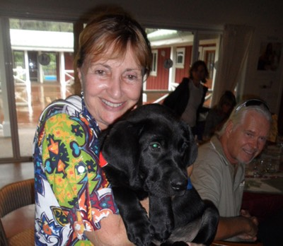 Makana Aloha founder, JoRene Valkirs with a puppy in training at Assistance Dogs of Hawaii